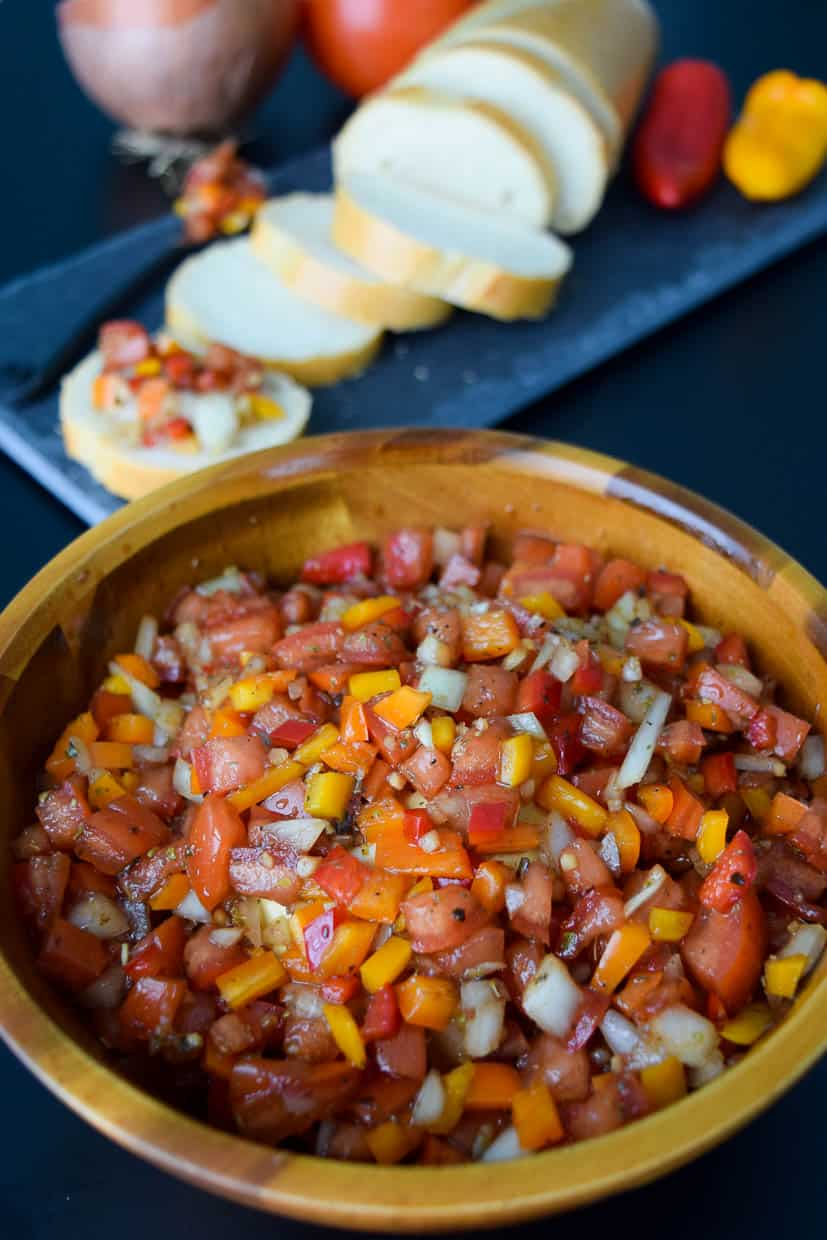 Bruschetta with Mini Peppers in wooden bowl close up view
