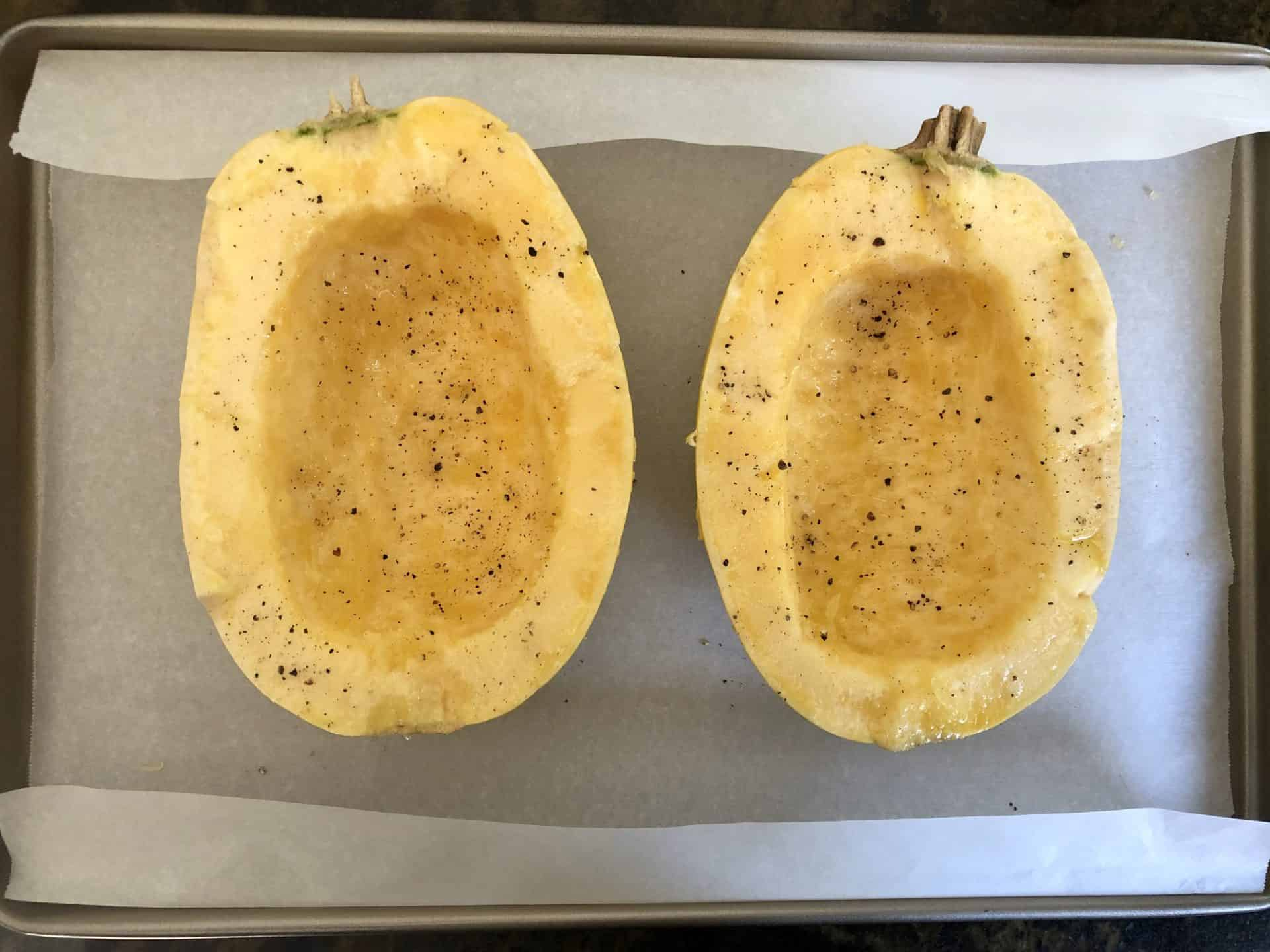 Spaghetti Squash on parchment paper lined baking sheet ready to be cooked