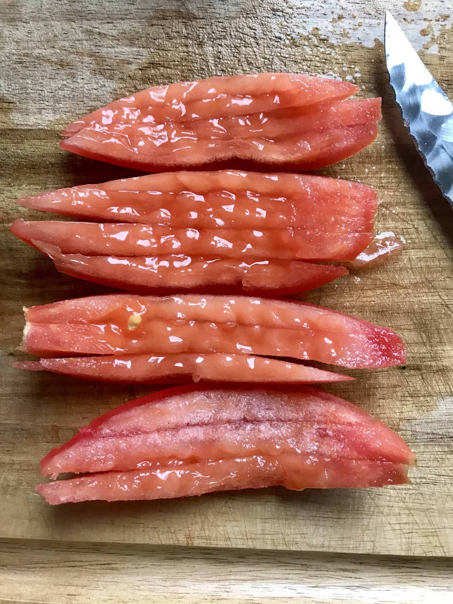 Tomato slices on wooden cutting board ready to be diced