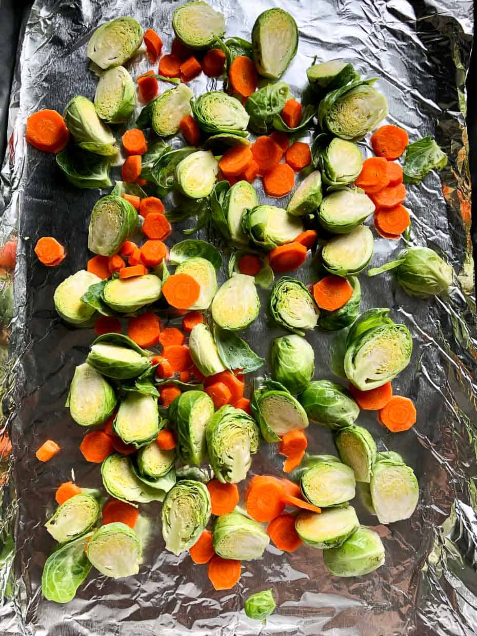 baking sheet lined with foil with Brussels sprouts and carrots ready to be roasted