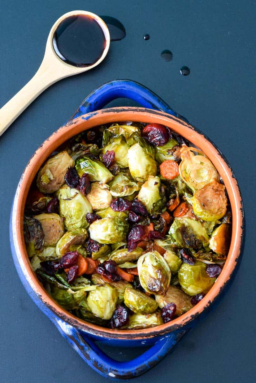 balsamic roasted Brussels sprouts in blue bowl on black chalkboard