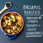 Balsamic roasted Brussels sprouts in blue bowl with chalkboard writing explanation of ingredients