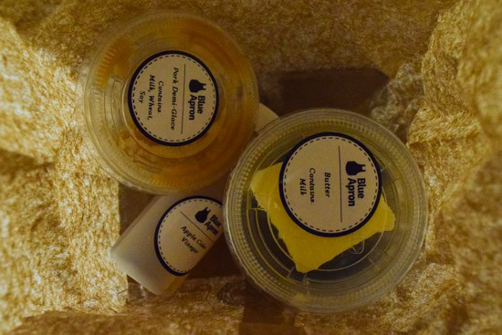 view inside of blue apron bag with small containers of seasonings