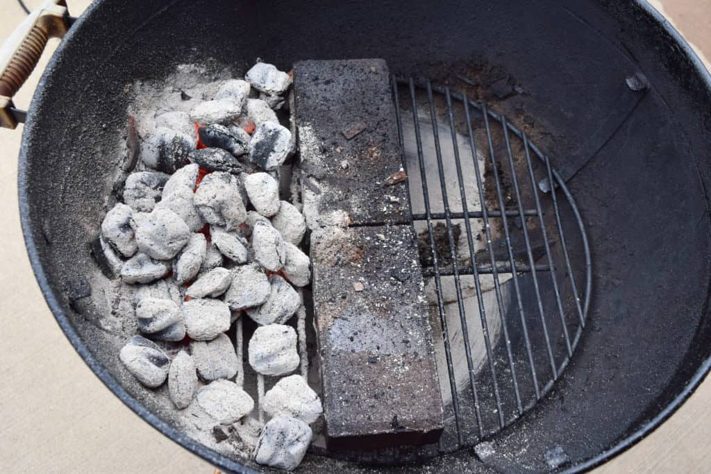 Grill set up for indirect heat with coals on one side and bricks in middle