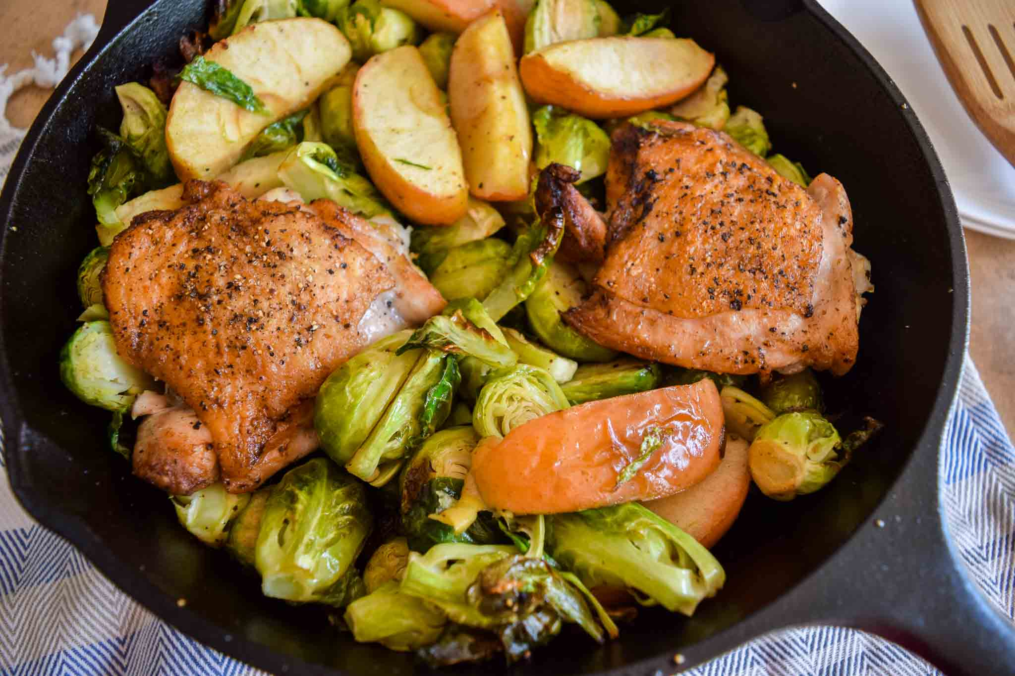 chicken and vegetables in cast iron skillet close up view