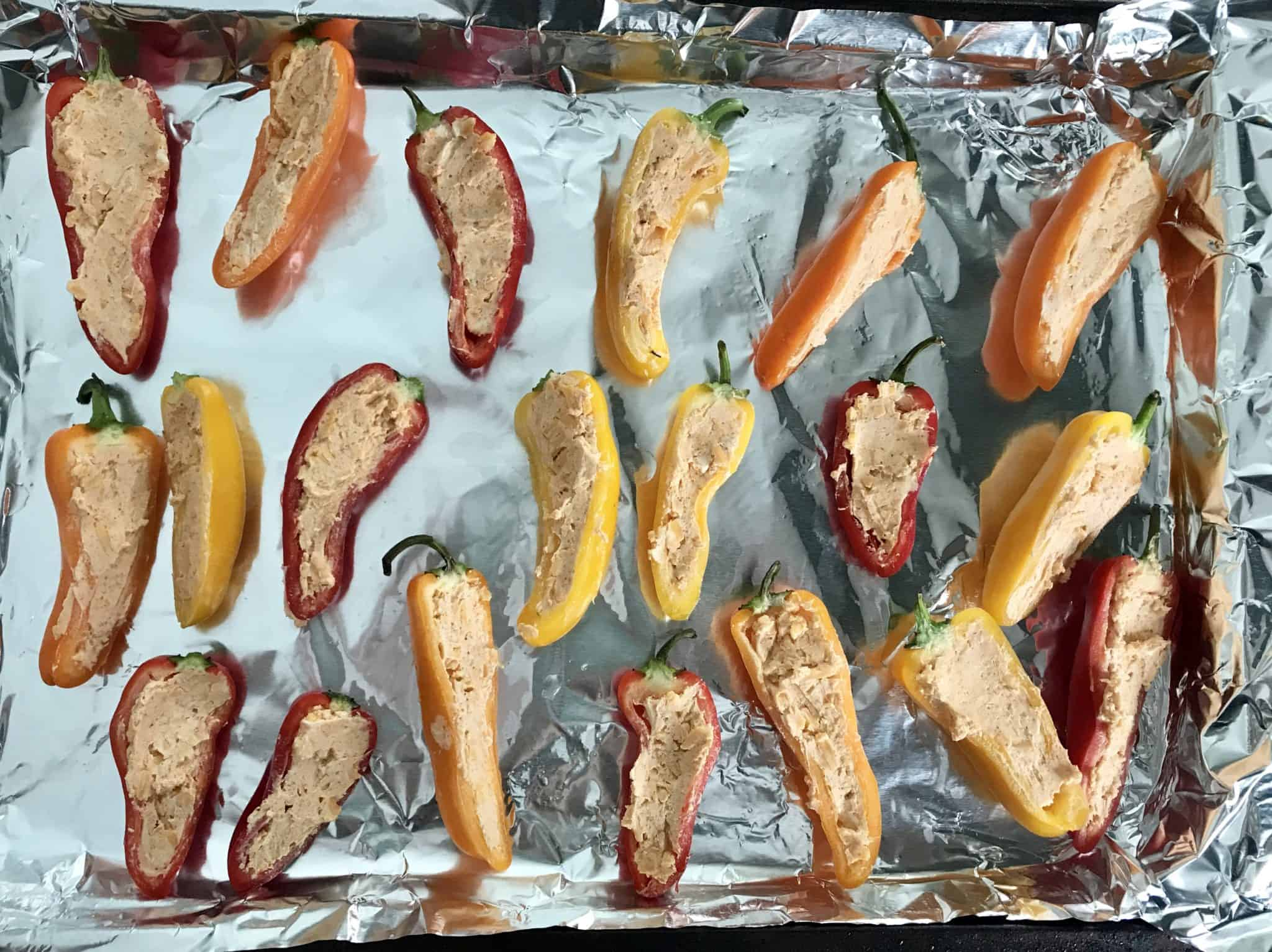 Mini peppers stuffed with cream cheese seasoning on baking sheet ready to be cooked
