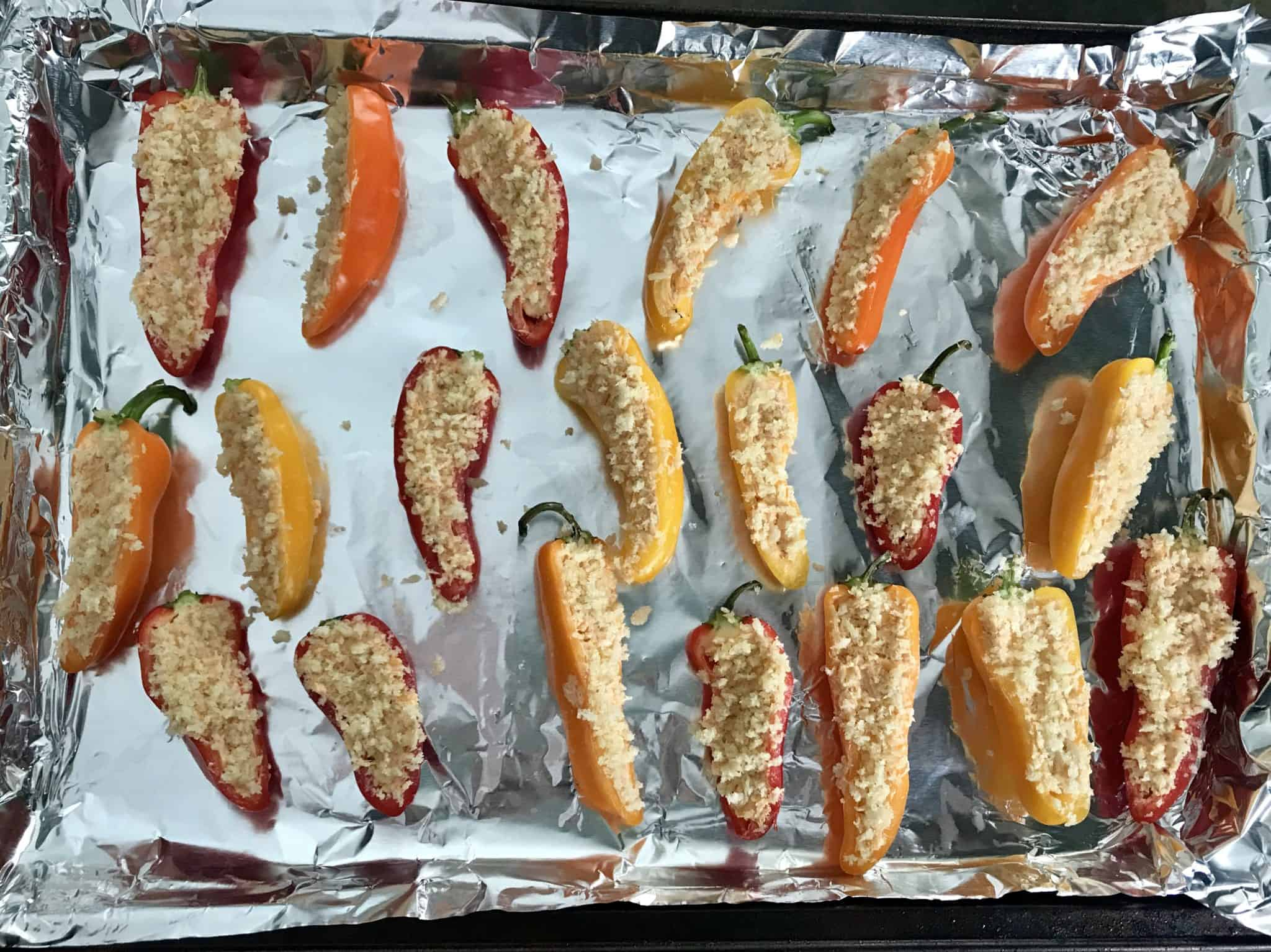 Mini peppers topped with bread crumbs ready to be baked overhead shot