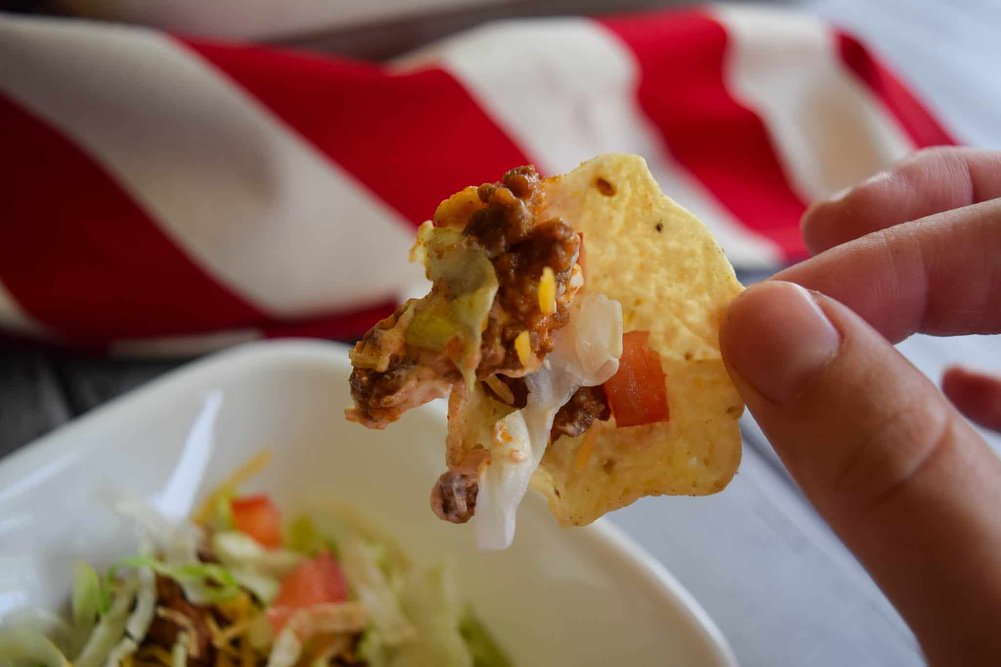 Taco dip scooped onto tortilla chip being held by hand close up view