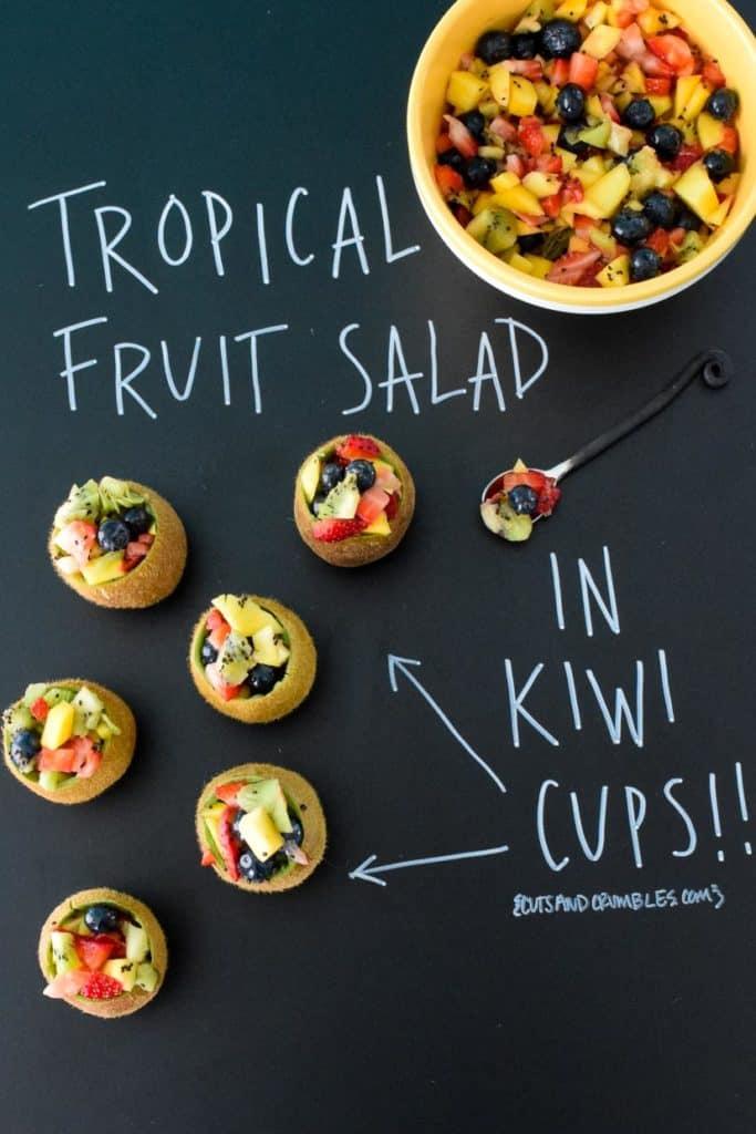 Tropical Fruit Salad in Kiwi Cups with title written on black chalkboard