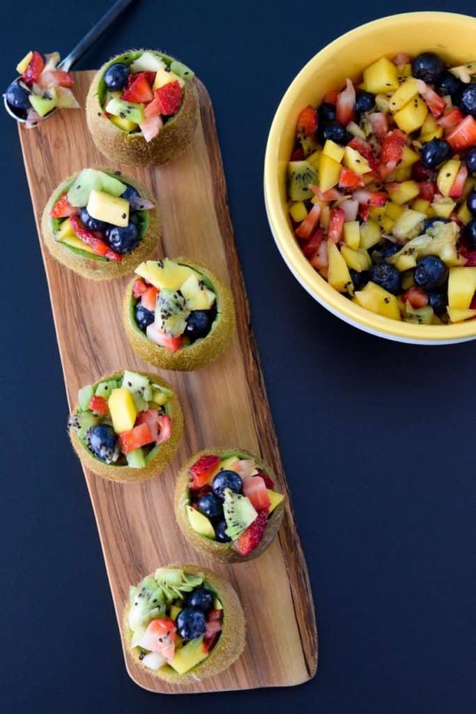 Tropical Fruit Salad in Kiwi Cups on wooden serving platter overhead shot