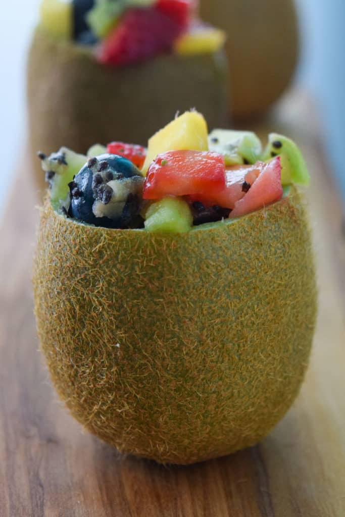 Close up side view of a kiwi stuffed with tropical fruit salad