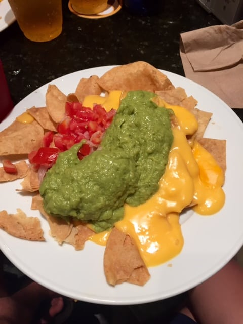 Messy plate of tachos topped with a huge pile of guacamole