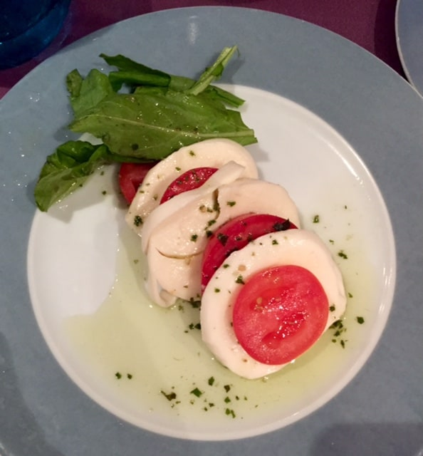 caprese salad on blue plate overhead shot