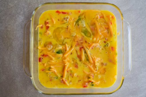 8x8 pan with raw eggs poured over casserole ingredients overhead shot