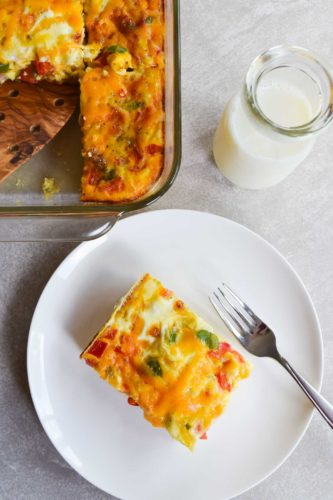 ham and egg casserole piece on white plate sitting beside casserole dish and jar of milk overhead shot
