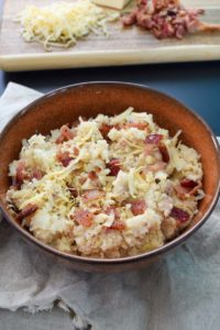 Smoked Gouda and Bacon Cauliflower Mash in brown rustic bowl close up view