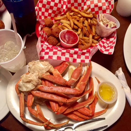 Plate of crab legs beside basket of hush puppies and french fries