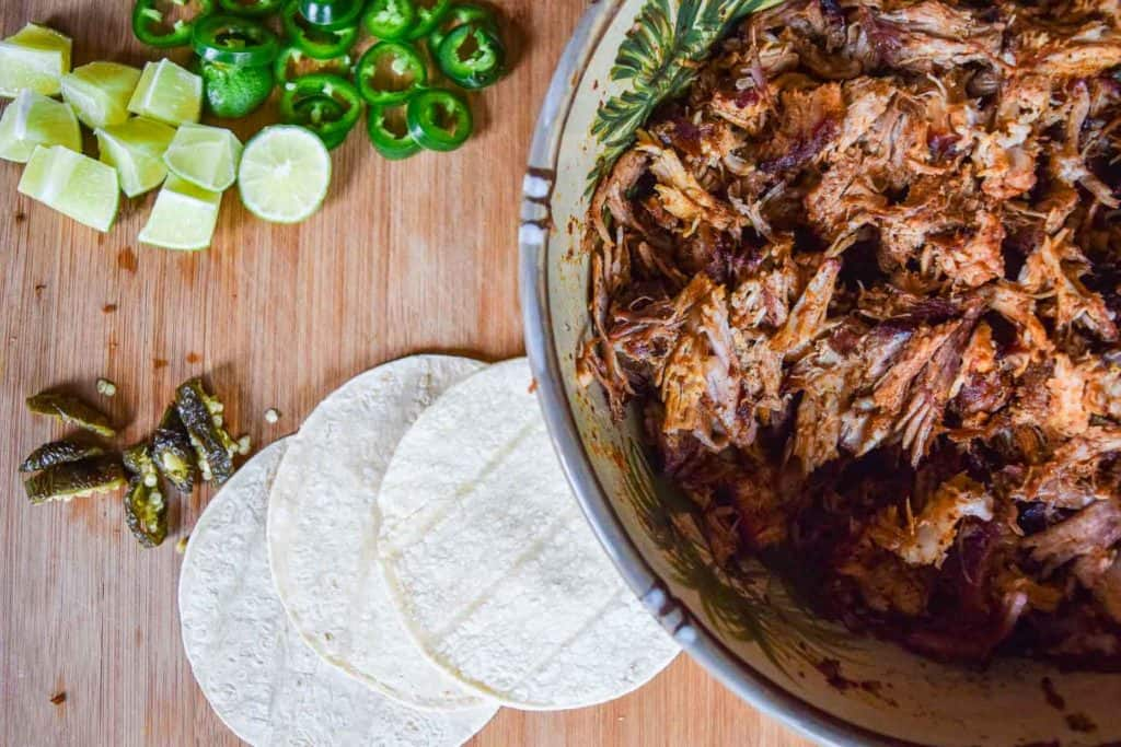 Smoked pork butt taco meat in bowl beside taco shells and vegetables overhead shot