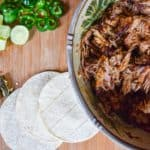 Smoked pork in bowl beside tortillas overhead shot