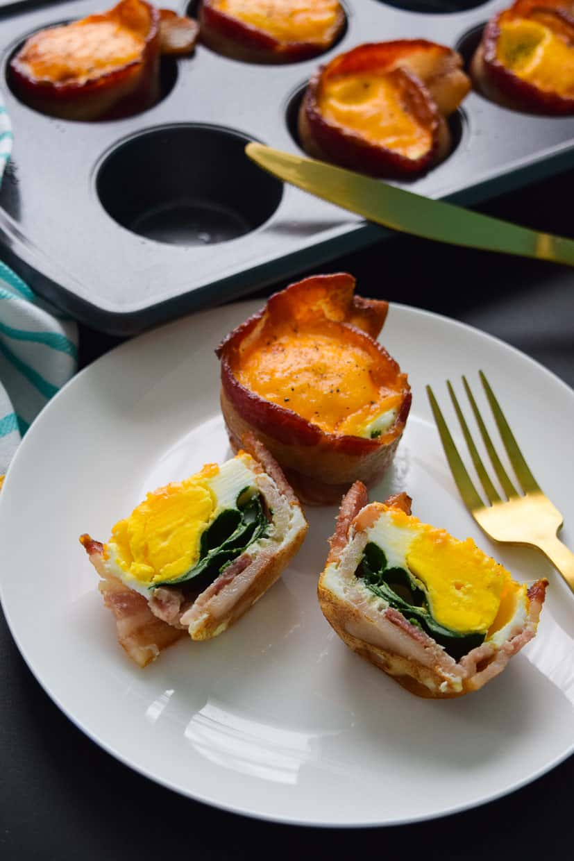 Bacon and cheese omelette cups sliced in half on plate with gold fork