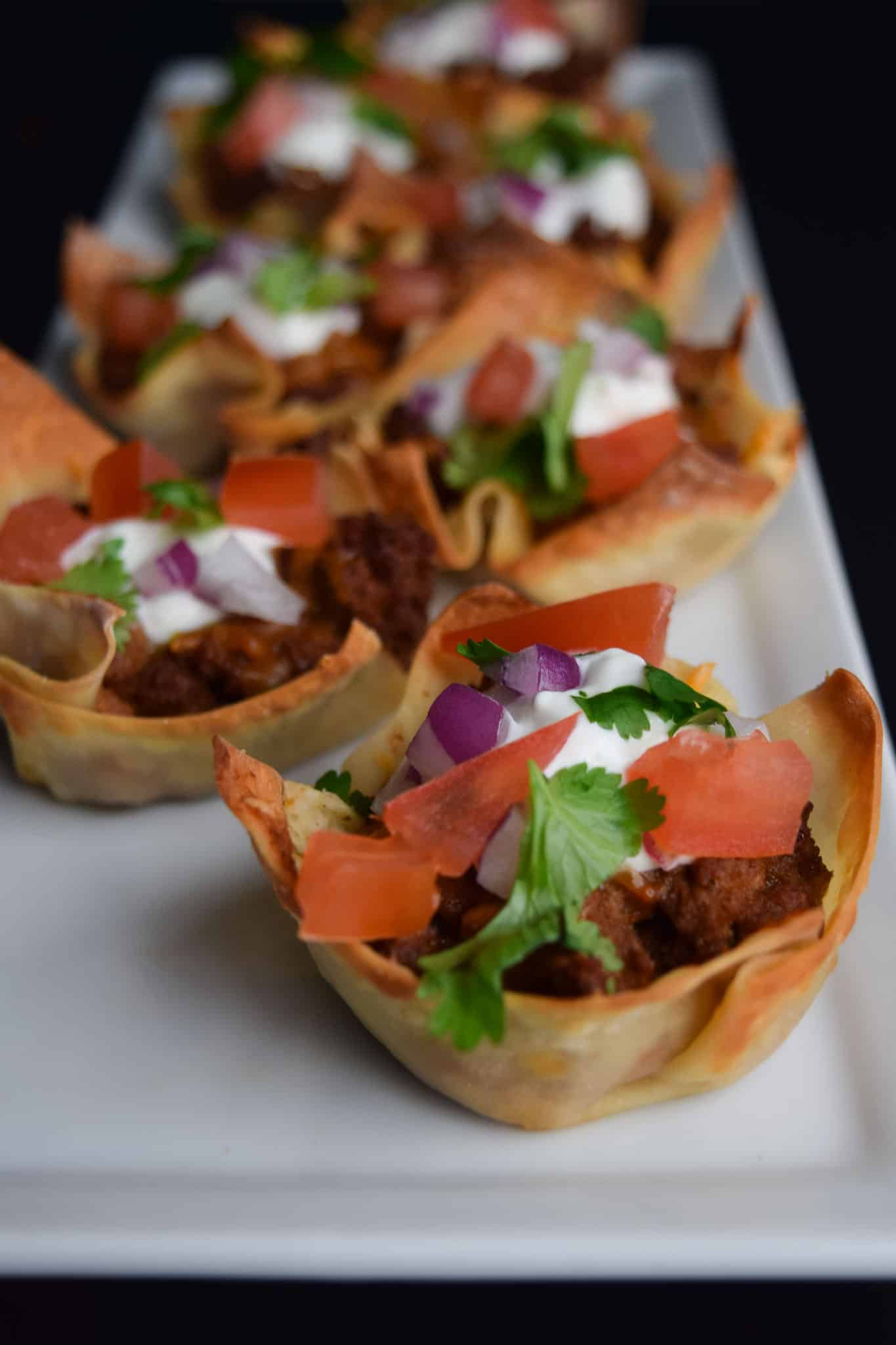 taco won ton cups on white platter ready to be served