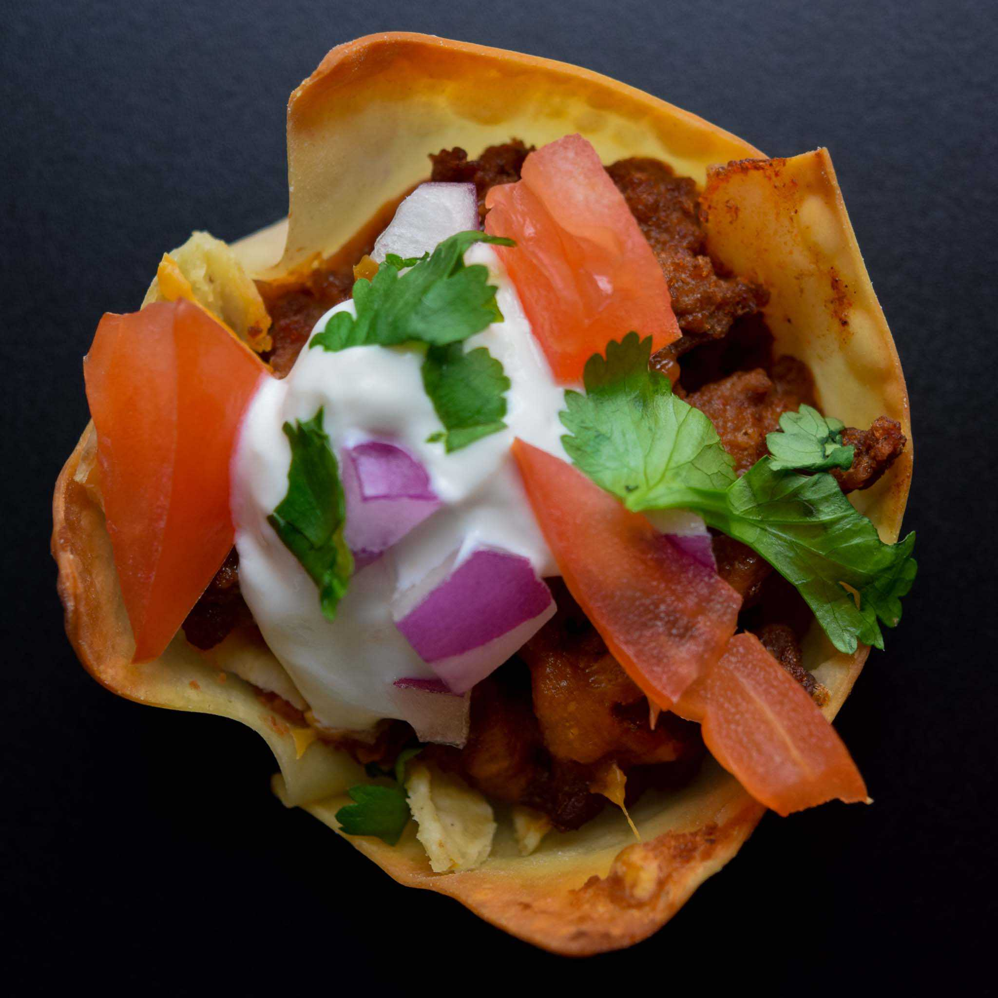 taco won ton cup topped with toppings overhead shot
