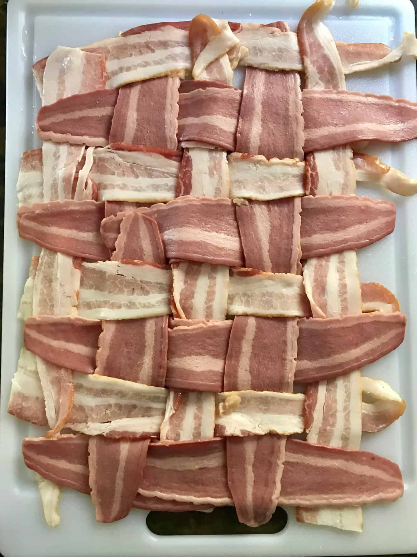 Bacon weave on white cutting board overhead shot