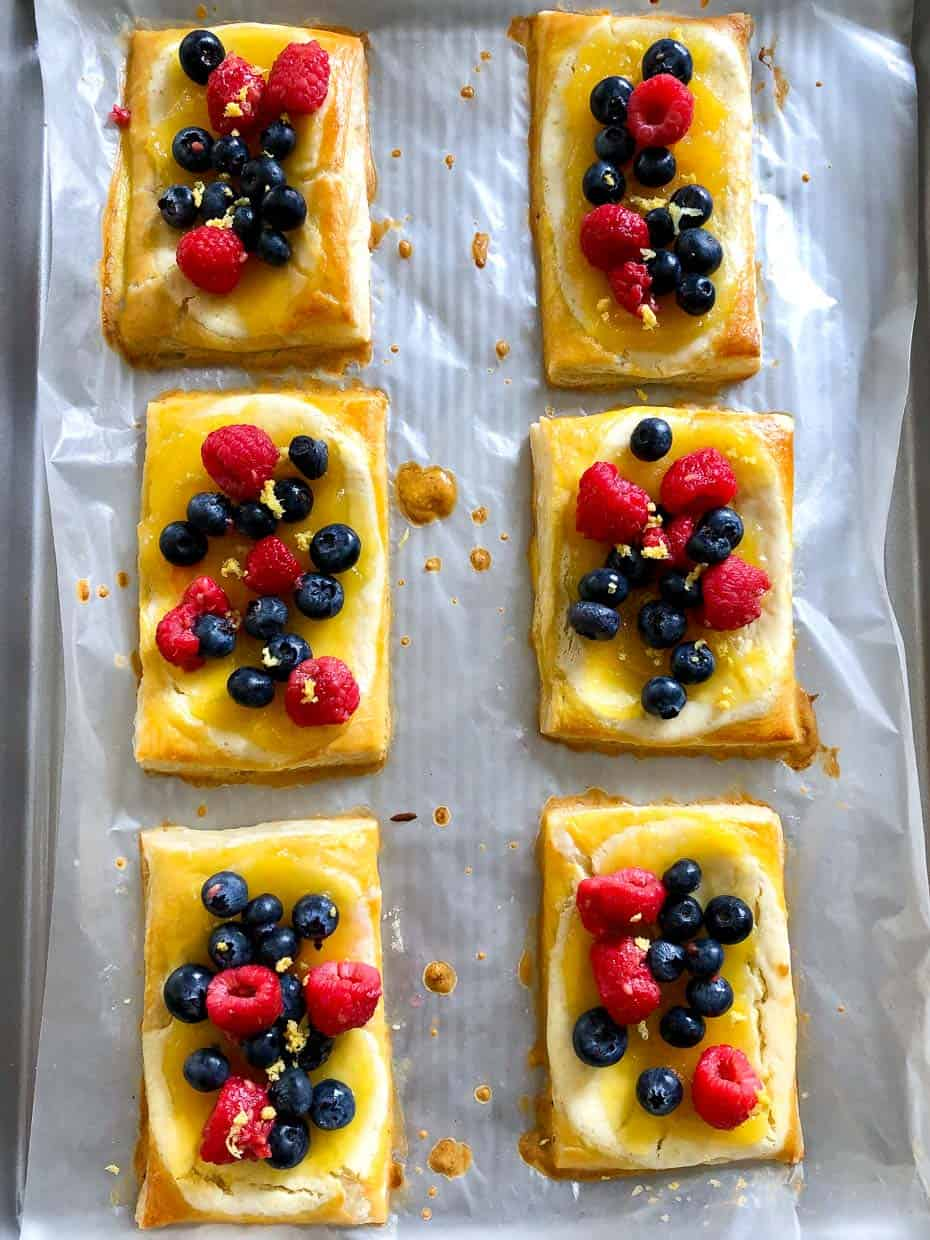 Lemon and berry cheesecake puffs on baking sheet
