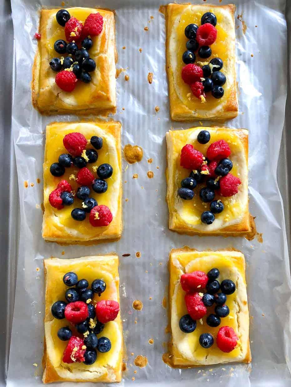Lemon and berry cheesecake puffs on baking sheet