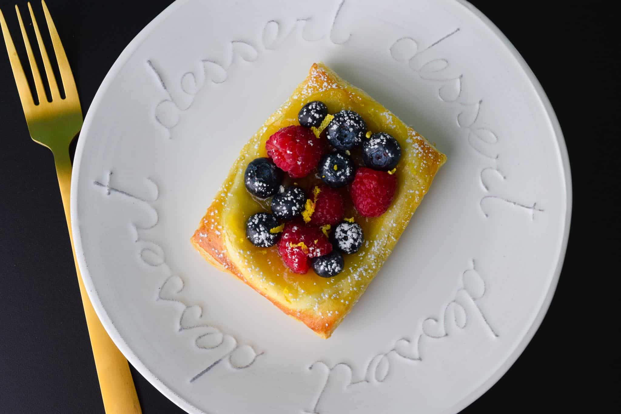 Lemon and Berry Cheesecake Puff on white dessert plate with gold fork overhead shot