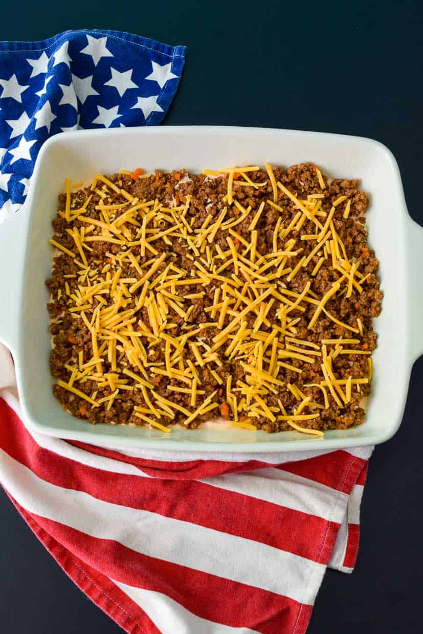 9x13 pan with ground beef topped with shredded cheese overhead shot