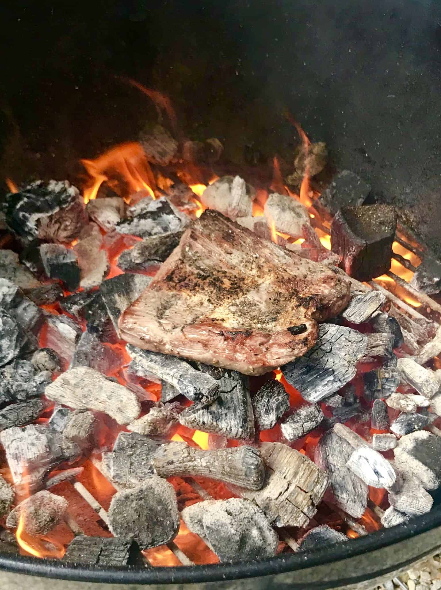 Steak being cooked directly on top of coals