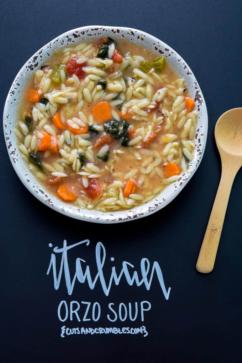 Italian Orzo Soup in rustic bowl with wooden spoon and title written on chalkboard