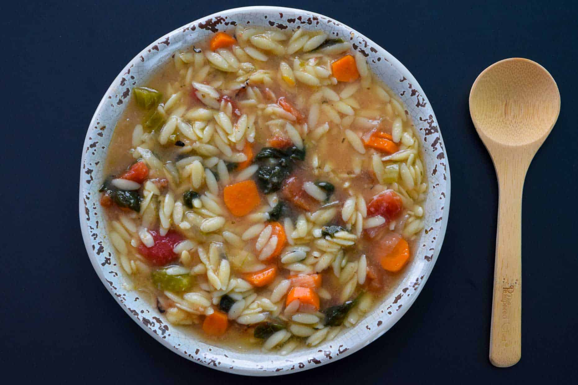 Italian Orzo Soup served in rustic bowl with wooden spoon overhead shot