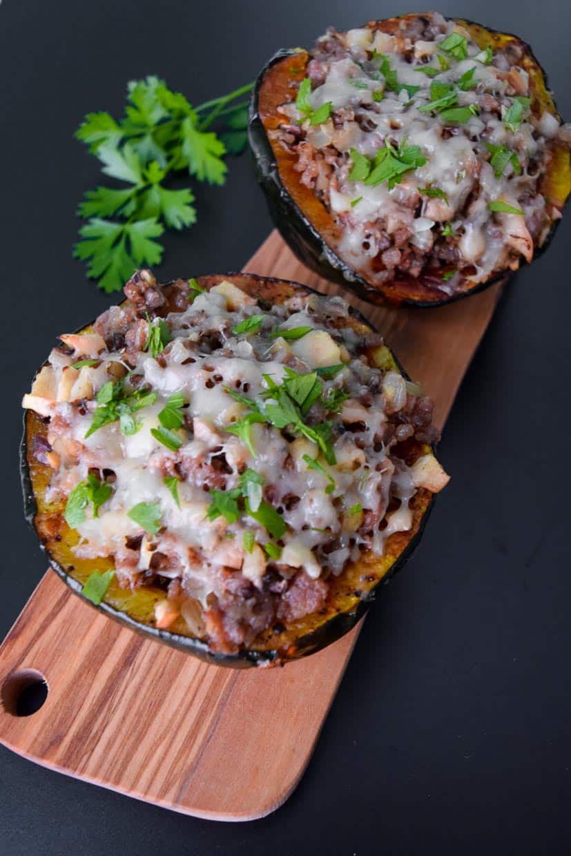 Stuffed Acorn Squash on wooden platter tapped with parsley