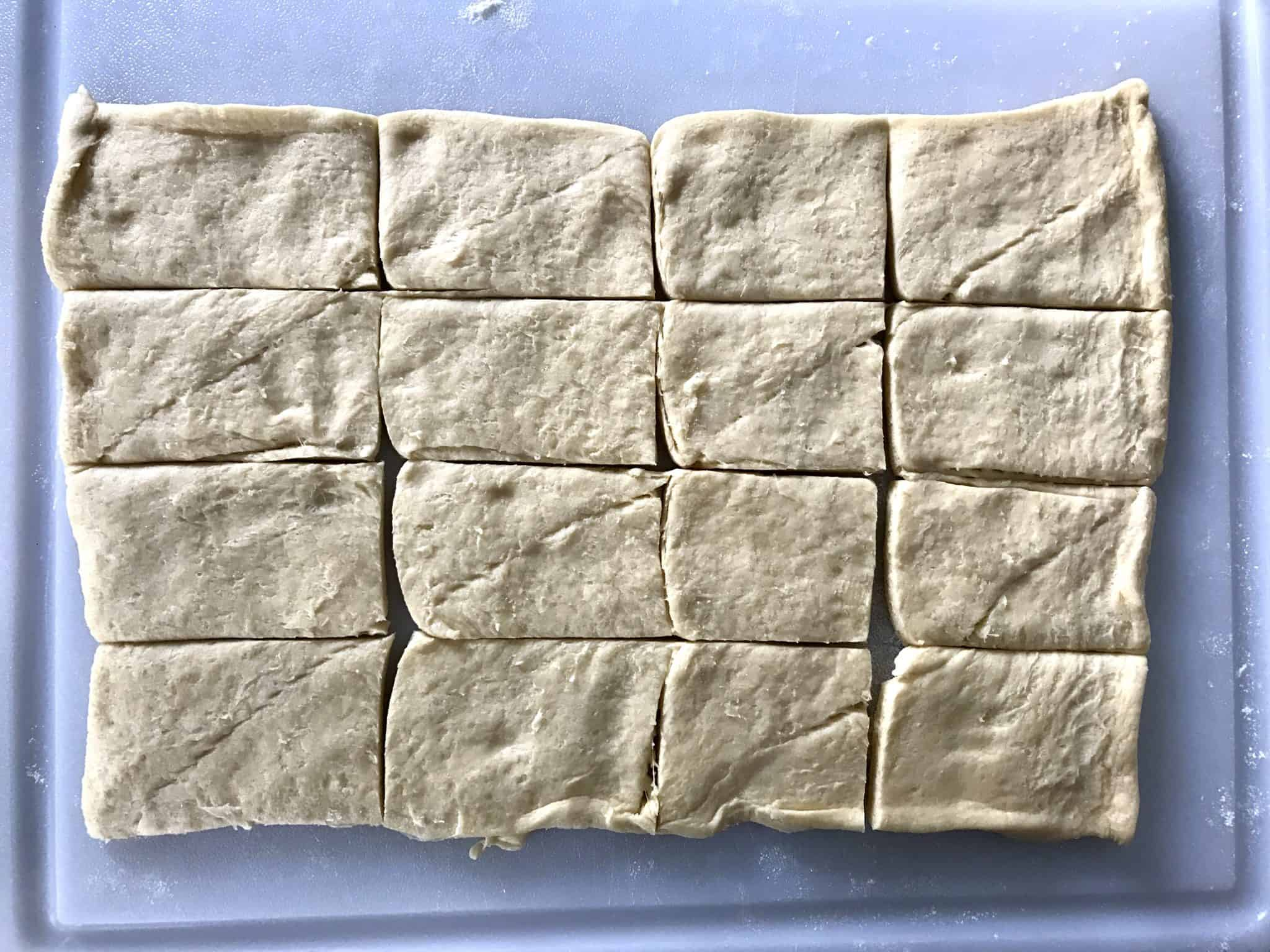 Puff pastry laid out on cutting board sliced into 16 rectangles overhead shot
