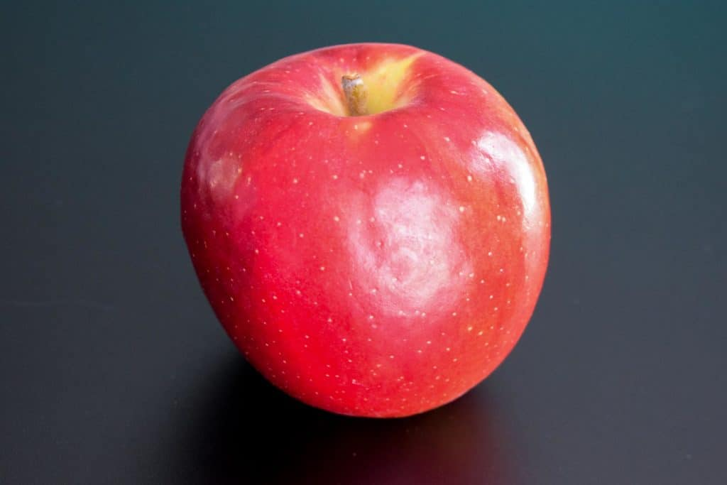 a red apple on a black background