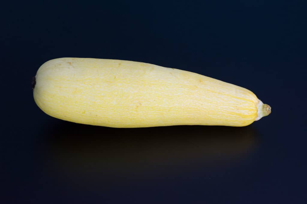 a yellow squash on a black background
