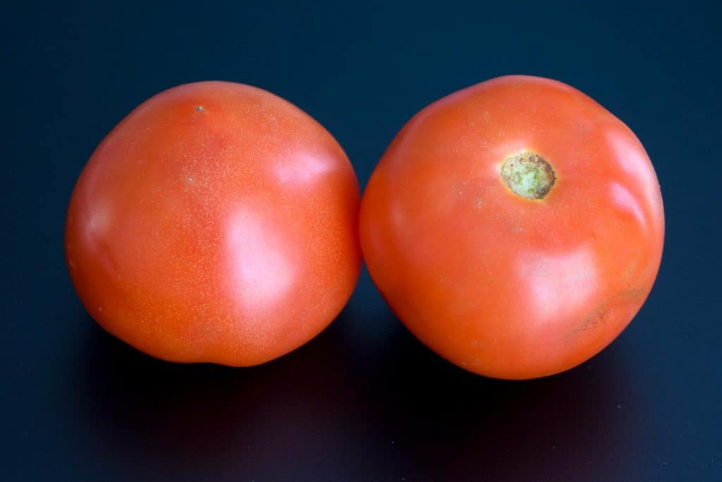 two red tomatoes on a black background