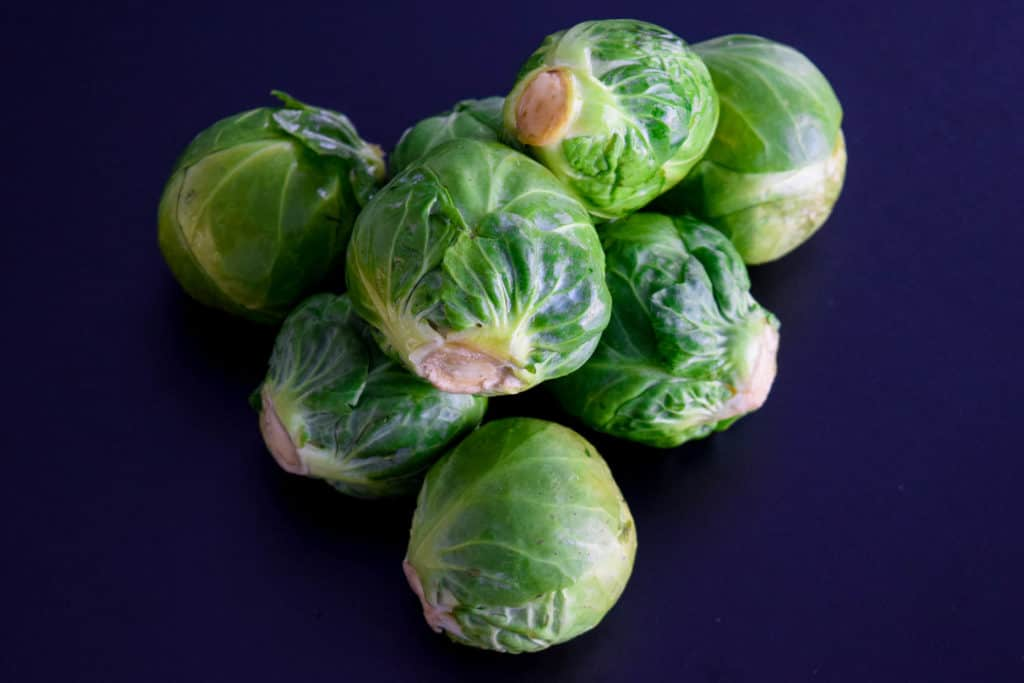 a pile of whole brussels sprouts on a black background