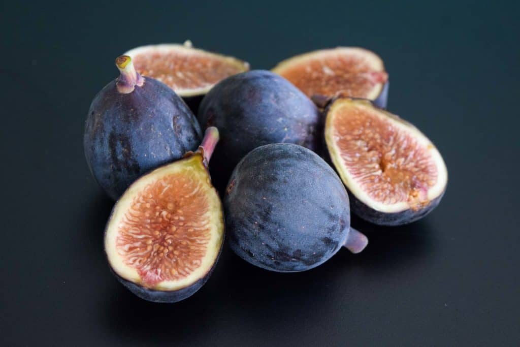 a pile of whole and halved figs on black background