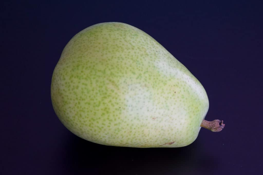 a green pear on a black background