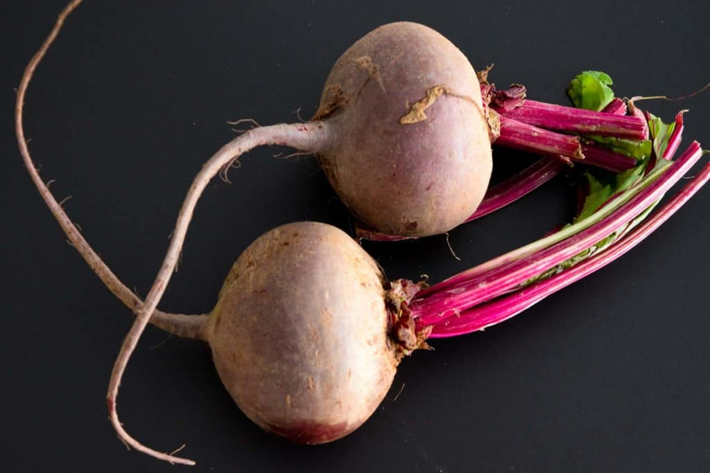 two beets on black background