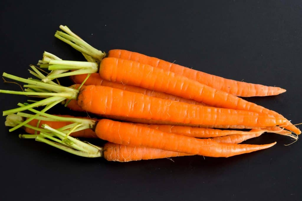 pile of carrots on black background