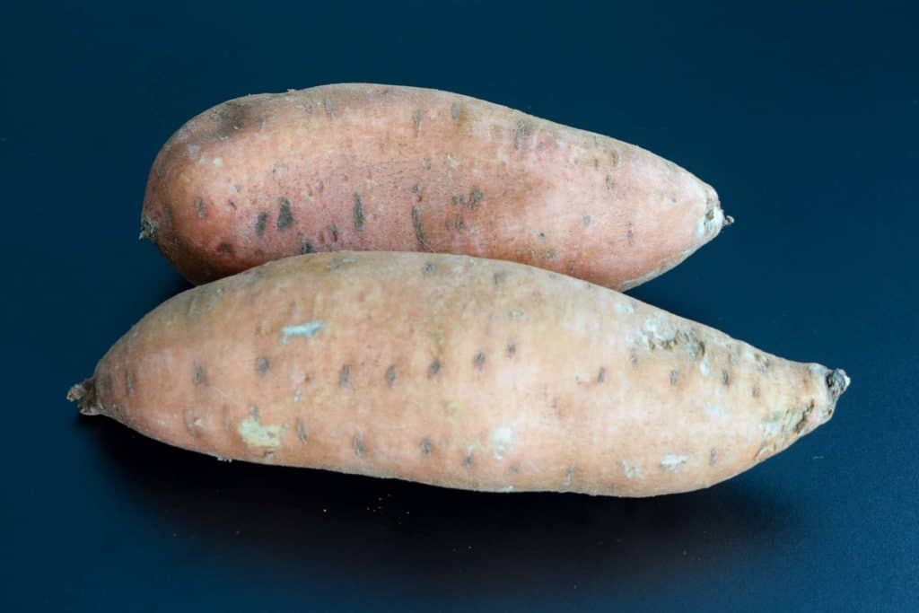 two sweet potatoes on black background