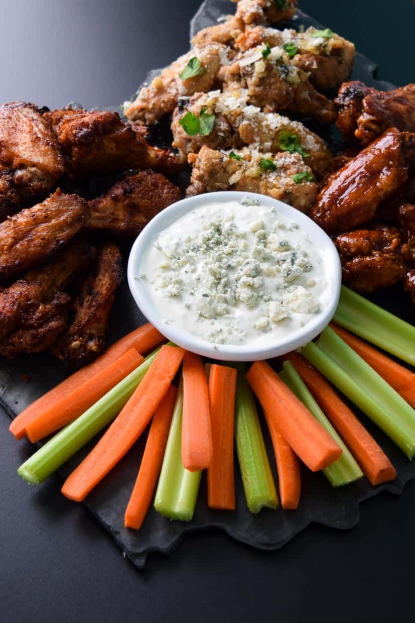 Air Fryer Game Day Wings in three flavors served on black platter with blue cheese celery and carrots up close view