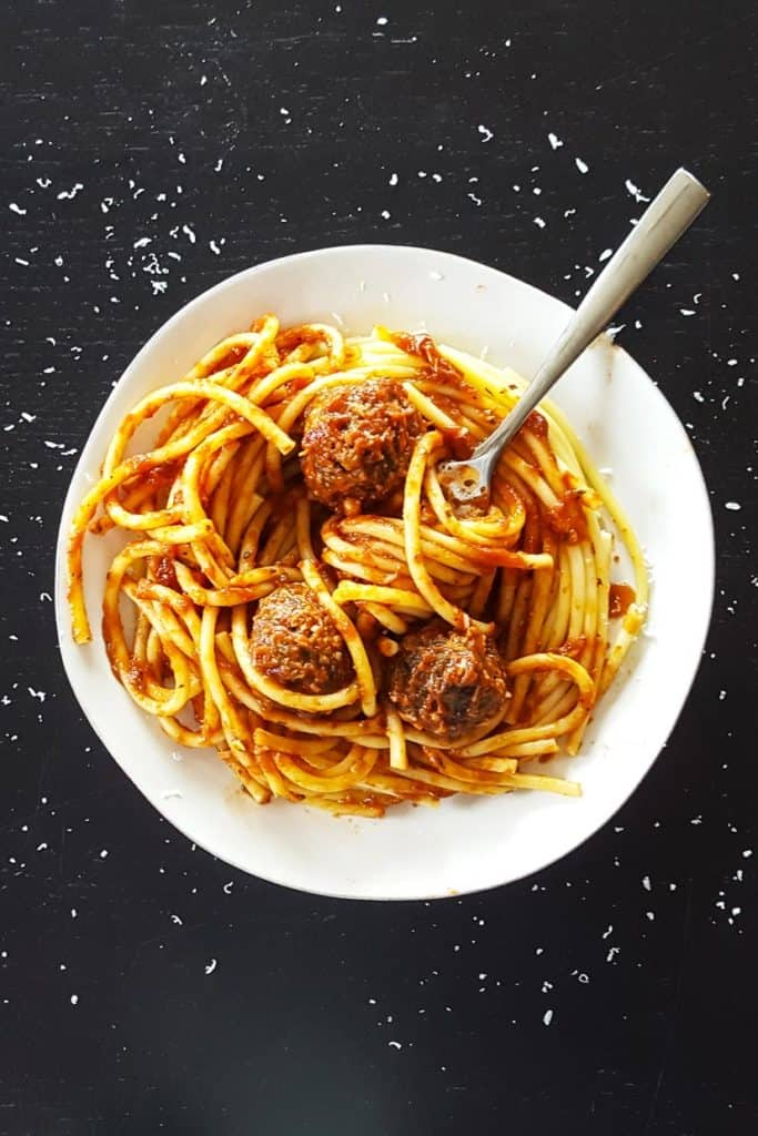 Spaghetti and meatballs in white bowl