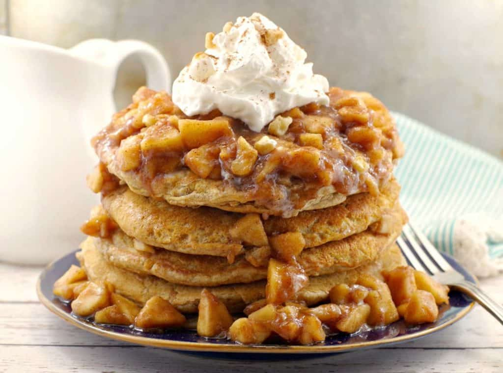 stack of pancakes topped with whipped cream