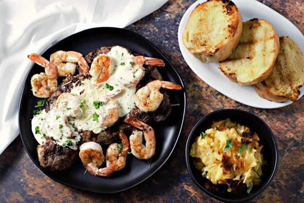 steak topped with shrimp and parmesan sauce