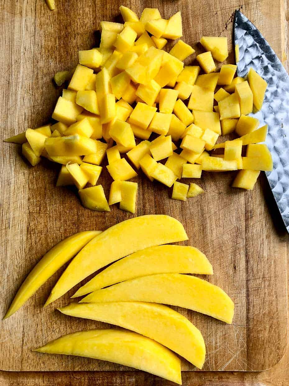 Diced mango and slices of mango next to knife on wooden cutting board